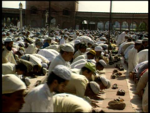 hundreds of muslim men kneeling and praying in unison india - 信者点の映像素材/bロール