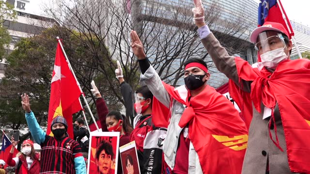 stockvideo's en b-roll-footage met hundreds of myanmar residents showing their 3-finger salutes and national league for democracy flags take to the streets in nagoya, japan on february... - salueren