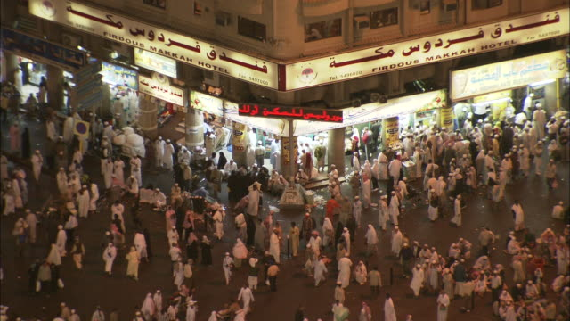 hundreds of pedestrians pass illuminated storefronts in saudi arabia. - saudi arabia stock videos & royalty-free footage