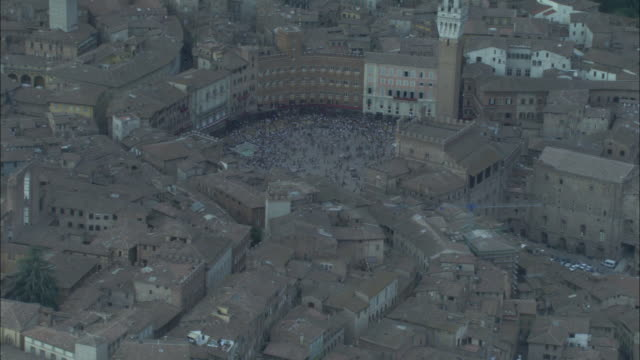 hundreds of people crowd the piazza del campo in siena, italy. - piazza del campo stock videos and b-roll footage