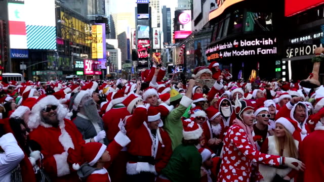 hundreds of people dressed santa claus and mrsclaus gather for the annual santa con festivities at the times square in new york on december 13 2014 - mrs claus stock videos and b-roll footage