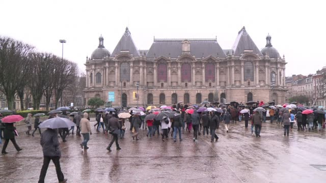 hundreds of people gathered in the rain in the french city of lille at midday to observe a minute of silence in honour of the 12 people killed by... - lille stock videos & royalty-free footage