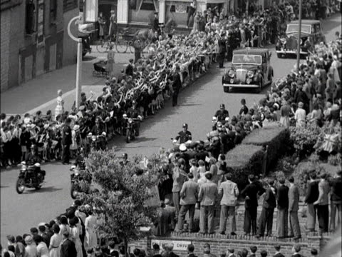 stockvideo's en b-roll-footage met hundreds of people greet the queen and prince philip as they arrive in wandsworth for a post coronation tour of london 1953 - wandsworth