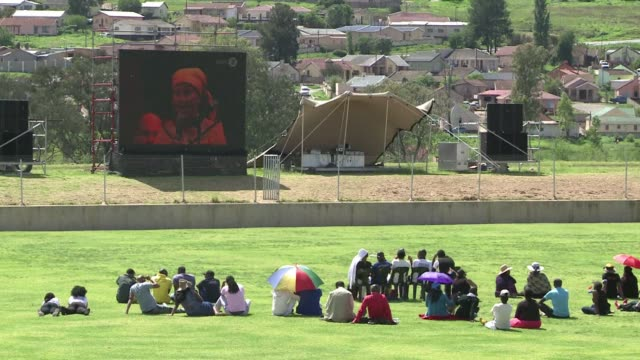 hundreds of people have gathered at stadiums in mthatha to watch the live broadcast of nelson mandelas state funeral happening nearby in qunu his... - live broadcast stock videos & royalty-free footage