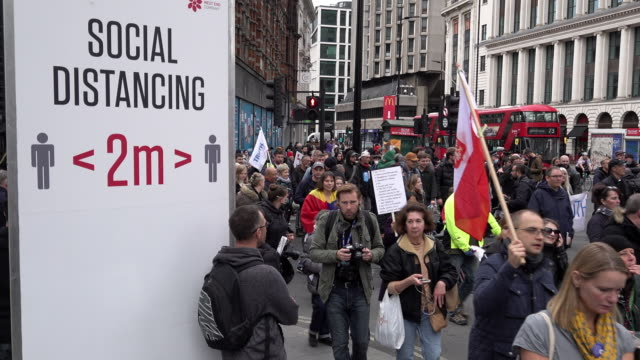 hundreds of people ignore social distancing measures and march past a two metre social distancing sign at oxford street on a protest promoting... - marching stock videos & royalty-free footage