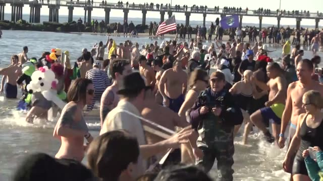 vídeos de stock, filmes e b-roll de hundreds of people in bathing suits run into the the atlantic ocean during the coney island polar bear club's 114th annual new year's day plunge on... - dia do ano novo