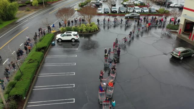 hundreds of people line up to enter a costco store on march 14, 2020 in novato, california. some americans are stocking up on food, toilet paper,... - 成一排 個影片檔及 b 捲影像