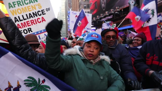 hundreds of people, many of them haitian, demonstrate against racism in times square on martin luther king day on january 15, 2018 in new york city.... - アフリカ系カリブ人点の映像素材/bロール