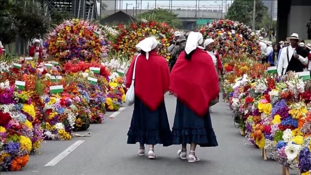 hundreds of people parade with ornate arrangements of flowers to close colombia's flower fair - medellin colombia stock videos & royalty-free footage