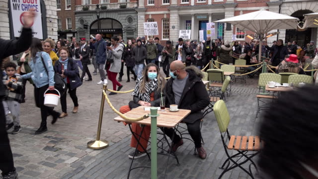 """hundreds of people shouting """"take off your mask"""" ignore social distancing measures and march past customers sat outside a restaurant in covent garden... - march month stock videos & royalty-free footage"""