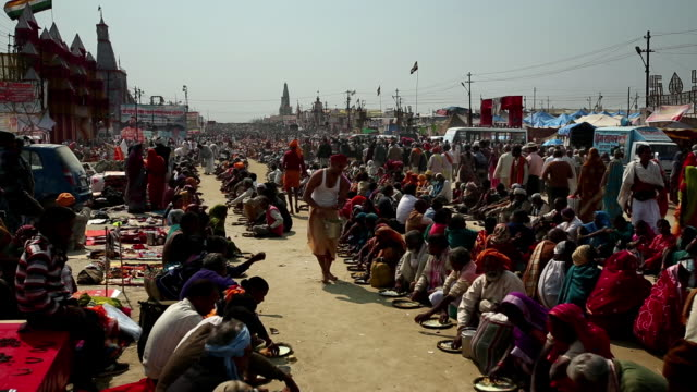 Hundreds of people sit on the ground in lines receiving and eating meals served by lunghi clad barefoot men with buckets of food. Kumbh Mela, India