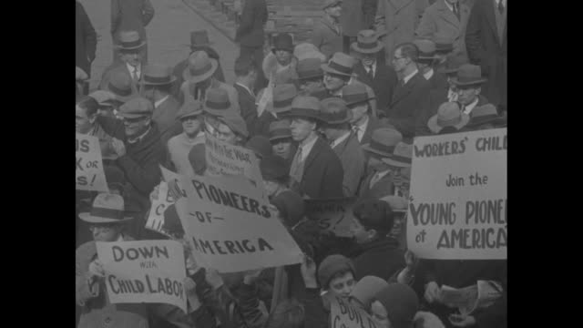 Hundreds of people some with signs Young Pioneers of America Down with child labor Workers' children join the young pioneers of America Build Council...