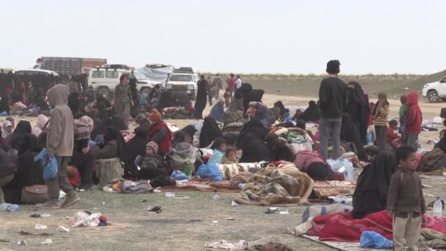 vídeos y material grabado en eventos de stock de hundreds of people wait to get on trucks that will take them to refugee camps after streaming out of the islamic state group's last syrian stronghold... - siria