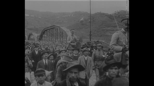 hundreds of portuguese men cross a bridge / men wait to board a packed passenger train / troops on departing train wave handkerchiefs outside the... - 1910 stock videos and b-roll footage