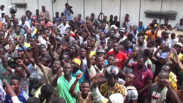 hundreds of protesters in benin man burning barricades to defy police and soldiers in unrest that follows a controversial election held without a... - benin stock videos and b-roll footage