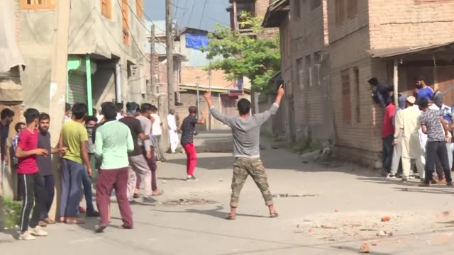 hundreds of protesters in indian administered kashmir clash with police who respond with tear gas rounds and pellet firing shotguns - jammu e kashmir video stock e b–roll