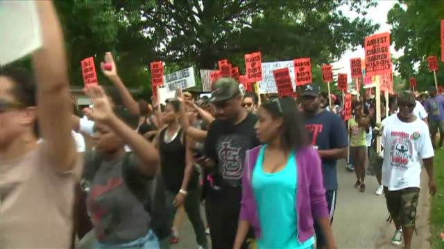 Hundreds of protesters march peacefully through the streets of Ferguson Saturday calling for justice three weeks after the fatal police shooting of...