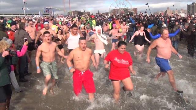 vídeos de stock, filmes e b-roll de hundreds of revelers race into the ocean in the famous coney island polar bear swim on new year's day - dia do ano novo