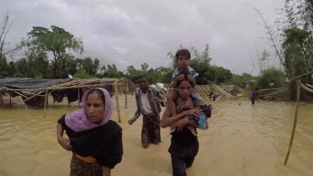 COX'S BAZAR BANGLADESH SEPTEMBER 20 Hundreds of Rohingya Muslims who fled Myanmar recently walk through floodwaters at a makeshift refugee camp and...