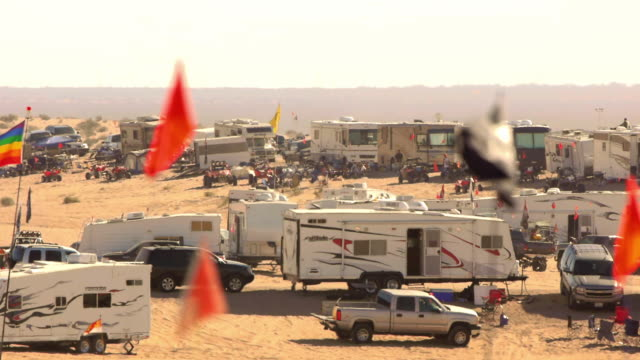 hundreds of RVs pick up trucks and off road vehicles in a large encampment during Thanksgiving weekend off road enthusiasts in the sand dunes of Glamis, California.