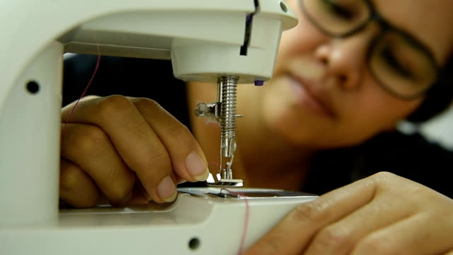 hundreds of sewing thread at sewing machine. - only mature women stock videos and b-roll footage