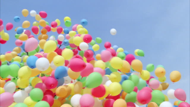 ms tu  hundreds of small multi-colored helium filled balloons as they rise into sky. - カラフル点の映像素材/bロール