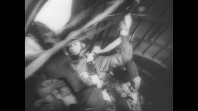 hundreds of soldiers in parachutes fall to the ground in dday rehearsal during wwii - fallschirmjäger stock-videos und b-roll-filmmaterial