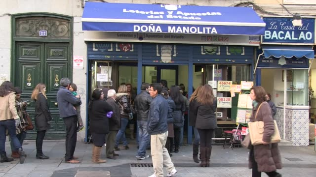 hundreds of spaniards queue to buy the annual end of year gordo lottery hoping to strike it big before christmas clean : spaniards queue for chance... - lotterie stock-videos und b-roll-filmmaterial