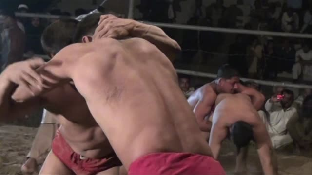 hundreds of spectators watch the traditional pakistani wrestling at a stadium in multan and cheer at the victory of the winner of the tournament - multan stock videos and b-roll footage