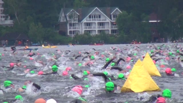 hundreds of swimmers in first leg of triathlon ironman lake placid - salmini 個影片檔及 b 捲影像