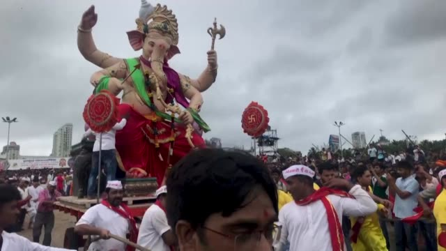 hundreds of thousands of worshippers throng the streets of mumbai for the immersion of thousands of elaborately decorated effigies of the hindu... - hinduism stock videos & royalty-free footage