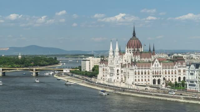 vídeos y material grabado en eventos de stock de parlamento húngaro en el día del cielo azul y el verano, budapest, vista lateral de lapso de tiempo de ángulo alto, en una curva del río danubio, alejarse - cultura húngara