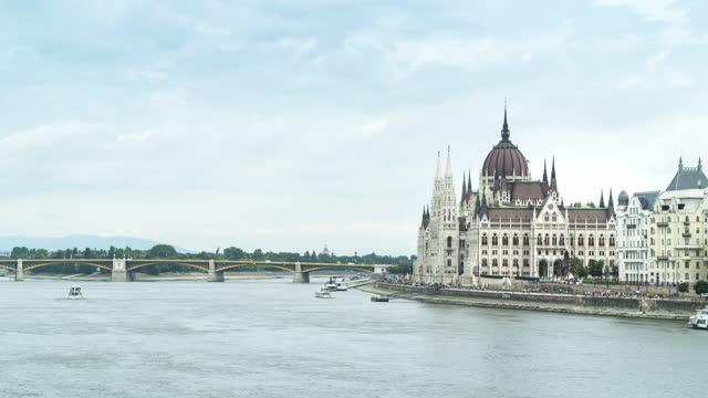 vídeos y material grabado en eventos de stock de parlamento húngaro en el día de fin de semana de cielo azul y verano, budapest, vista de lapso de tiempo, carretera de transporte a lo largo del río danubio - cultura húngara