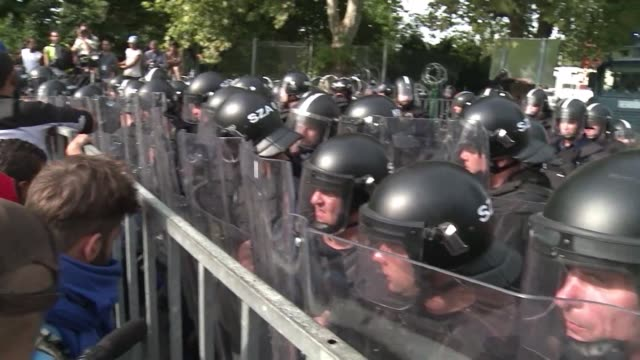 vídeos de stock, filmes e b-roll de hungarian police fire tear gas and water cannon at several hundred migrants protesting at being unable to cross the border from serbia - cultura do leste europeu