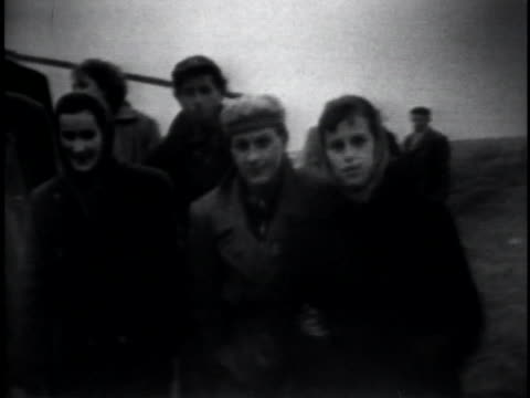hungarian refugees trudge along a country road as they leave their country during the hungarian revolution. - ungarische kultur stock-videos und b-roll-filmmaterial