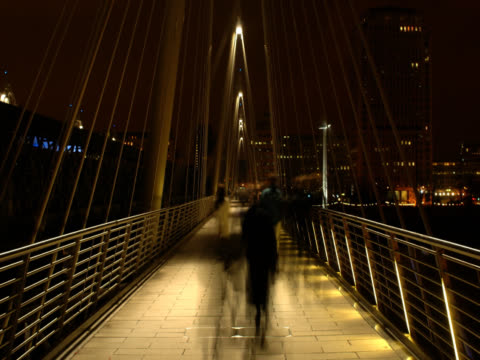 hungerford bridge filmed at night. shot in timelapse, with the camera pointed directly down the centre of the bridge, the low-level lighting reveals the blurred forms of pedestrians. london, uk - low lighting stock videos & royalty-free footage