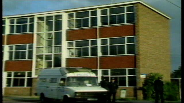 20 years on LIB Police van outside school building ZOOM IN broken upstairs window END LIB
