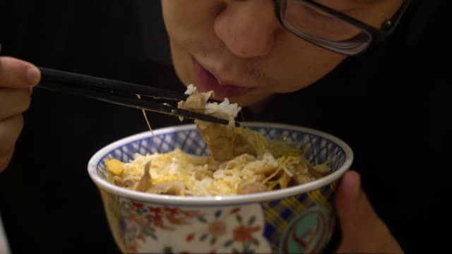 4k cu 空腹のアジア人男性が牛丼を食べる - fast food点の映像素材/bロール