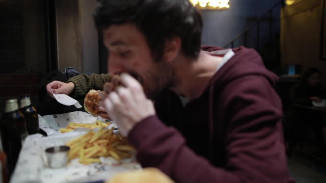 hungry couple in fast food restaurant - fast food stock videos & royalty-free footage