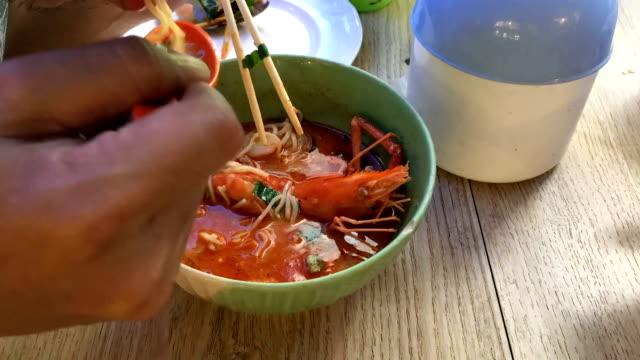 vídeos de stock, filmes e b-roll de com fome come macarrão - comida salgada