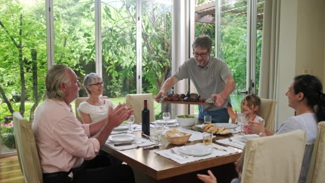 vidéos et rushes de famille affamée applaudissant l'arrivée de la viande grillée pour le déjeuner - barbecue vie sociale