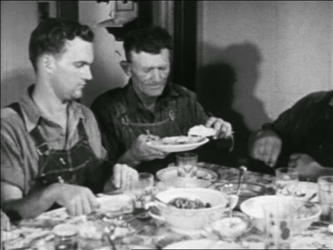 stockvideo's en b-roll-footage met b/w 1938 pan hungry farmhands at table passing plate of pie / man at end gets no pie / educational - 1938