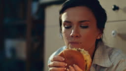 Hungry girl eating burger on floor. Young woman drinking red wine at home.