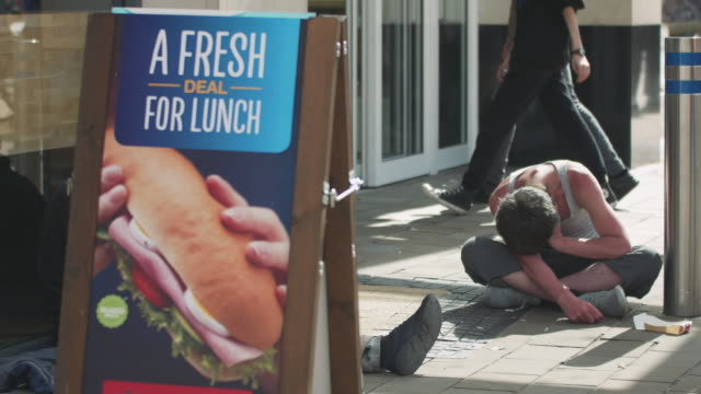 vidéos et rushes de hungry homeless man sitting on sidewalk in city beside food sign - avoir faim