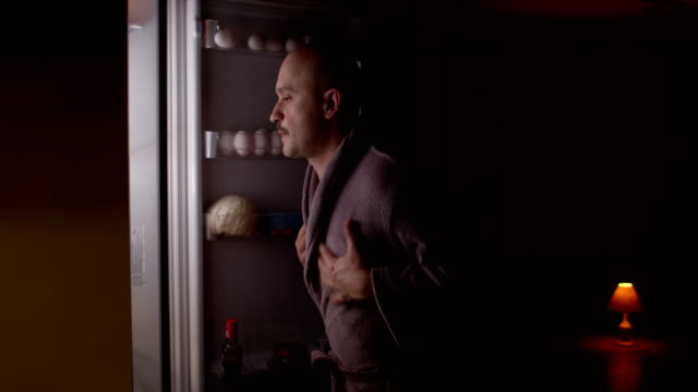 vidéos et rushes de hungry man eating food at night opening refrigerator and taking plate shot on red epic - minuit