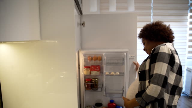 Hungry pregnant woman opening refrigerator