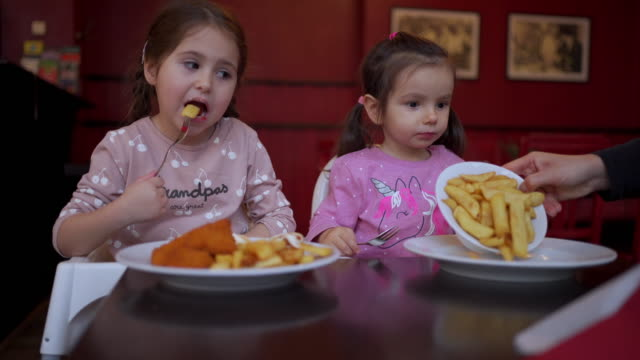 hungry sisters eating fries and chicken - prepared potato stock videos & royalty-free footage