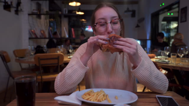 hungry woman biting her burger - cheeseburger stock videos & royalty-free footage