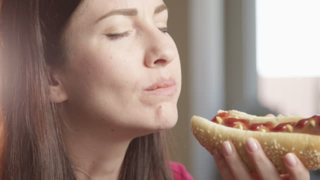 hungry woman eating hot dog enjoying the taste indoors with sun shining a close up shot on red camera - unhealthy eating点の映像素材/bロール