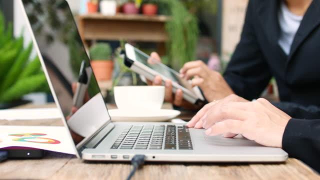 vídeos y material grabado en eventos de stock de hunman dos manos de gente de negocios con tablet y portátil hablar de un proyecto en una cafetería - business talk frase corta